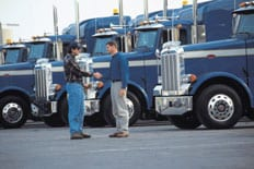 An instructor shaking hands with a fleet training graduate, in front of a row of semi-tractor trucks